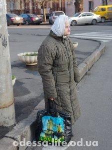 Бабушка с модной сумкой идёт из храма на остановку.