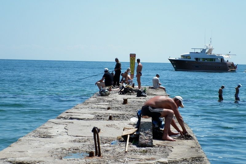 Рыбаки собираются на пирсе