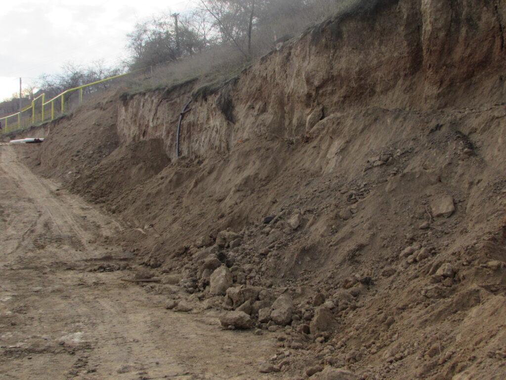 Новые небольшие обвалы склона, где строится дорога для грузовиков