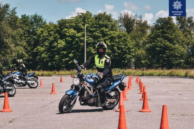 полицейский учится водить мотоцикл