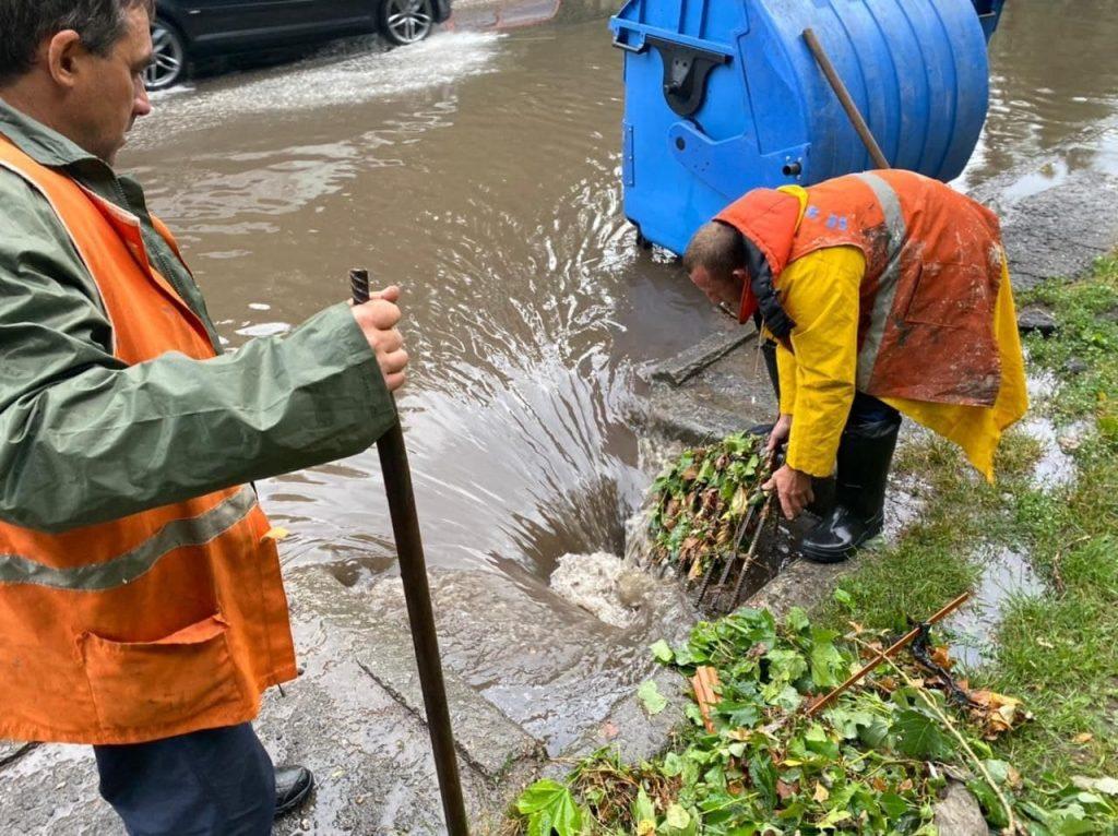 рабочие чистят ливневку